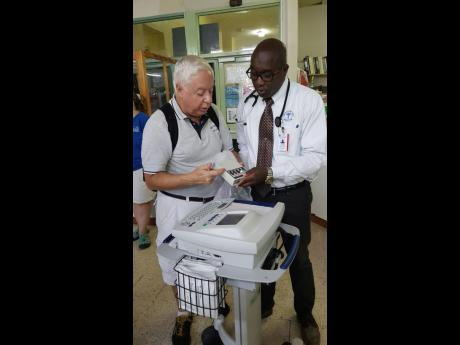Ernie Sandona (left), biomedical engineer and Issa Trust Foundation volunteer, demonstrates some of the modern features of the state-of-the art ECG machine to Dr Vincent Riley, cardiologist.